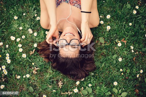 Teenage girl relaxing in the park and listening to the music
