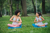 istock Happy girl exercising yoga and looking at female instructor next to her 1023555250