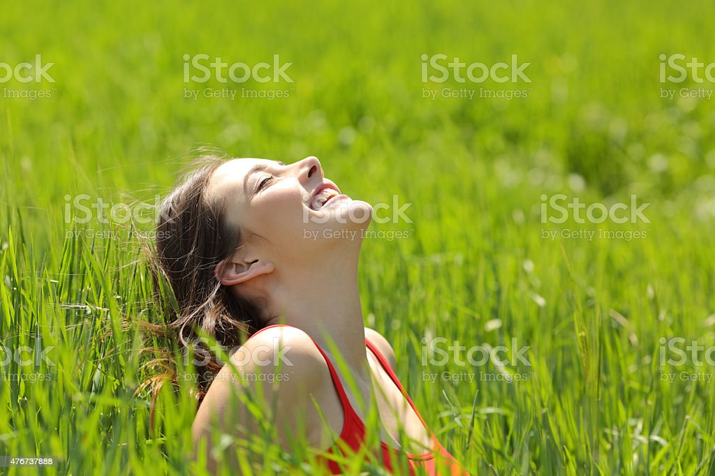 Happy girl face breathing fresh air in a meadow stock photo