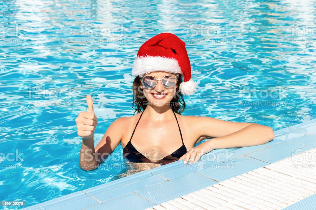 Happy Girl Face In Christmas Hat Shows Thumbs Up In Swimming Pool Summer Vacations Stock Photo Download Image Now Istock