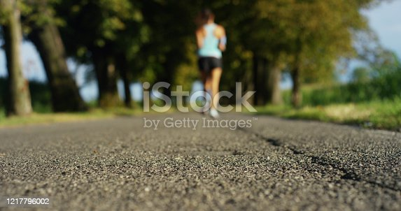 A happy girl fit relaxed jogging and running in a street with trees and nature, using headphones for music and run slow in sunset. concept of happiness for sports and fitness relaxation in nature
