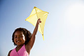 Cute African American girl, 7 years, flying a kite