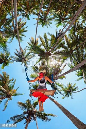 istock Happy girl flying up high on swing among palms 889538848