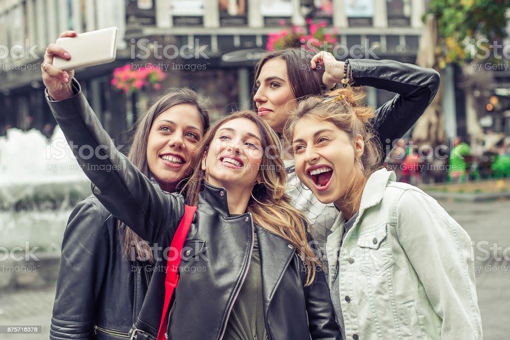 Happy girl friends taking selfie photos in the street stock photo