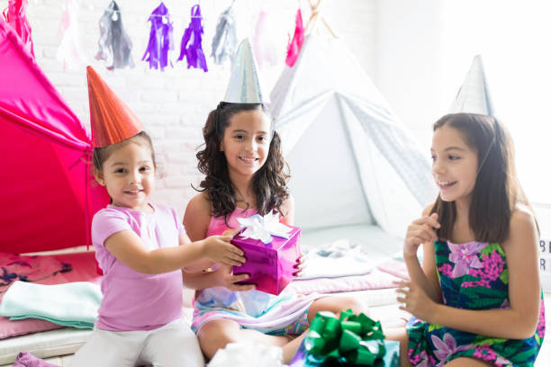 Happy Girl Giving Birthday Present To Friend During Pajama Party Happy little girl giving birthday present to friend during pajama party at home group of friends giving gifts to the birthday girl stock pictures, royalty-free photos & images