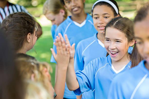 happy girl giving other team high fives after good game - kinder die schnell arbeiten stock-fotos und bilder