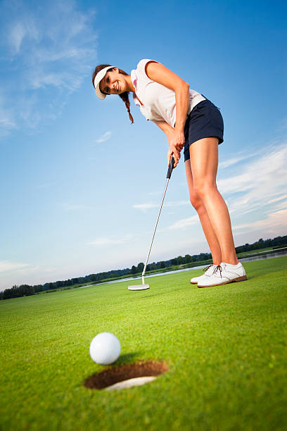Happy girl golfer putting ball into hole. stock photo