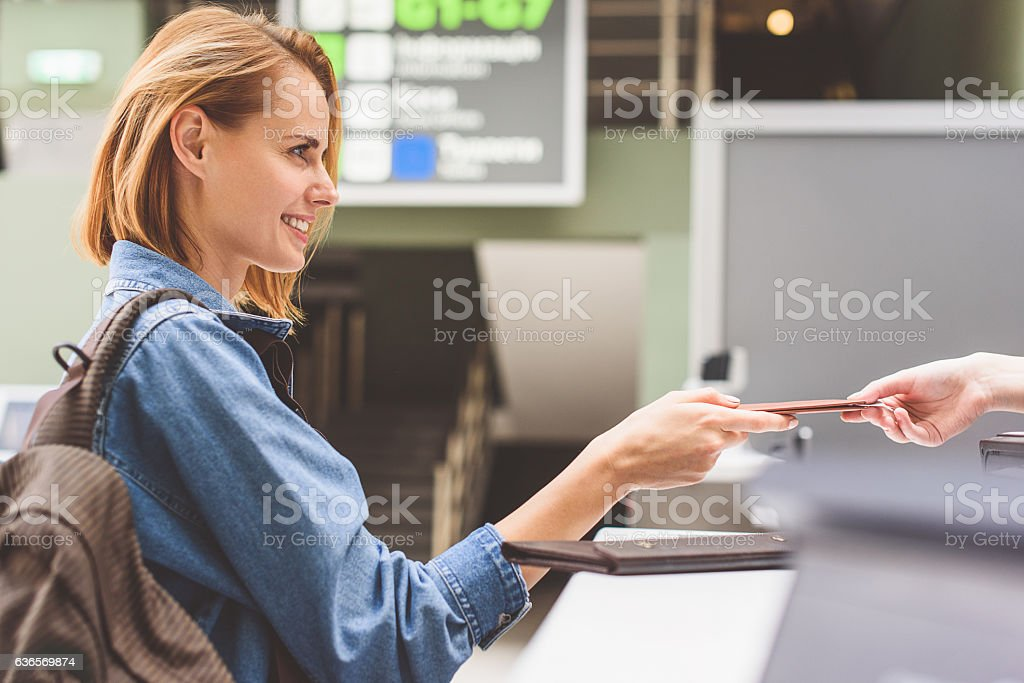 Happy girl handing over passport in airport stock photo