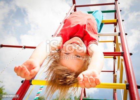 istock Happy girl hanging from a jungle gym in a summer garden 694095024