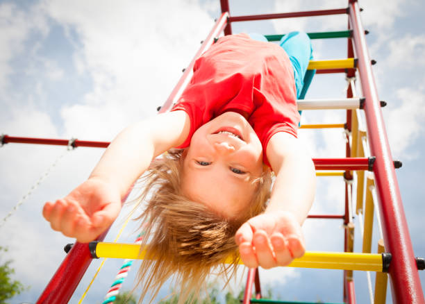 Happy girl hanging from a jungle gym in a summer garden stock photo