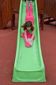 Happy girl having fun and sliding on outdoor playground