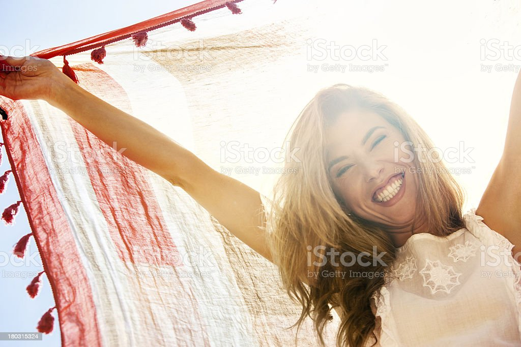 Happy girl hiding from sunlight under scarf. royalty-free stock photo