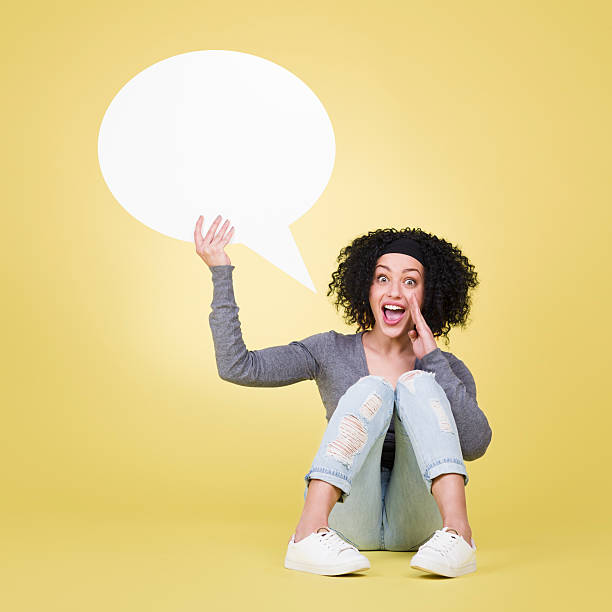 Happy girl holding a speech balloon with copy space. stock photo