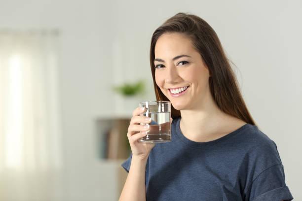 glückliches mädchen mit einem transparenten glas wasser - wasser trinken abnehmen stock-fotos und bilder
