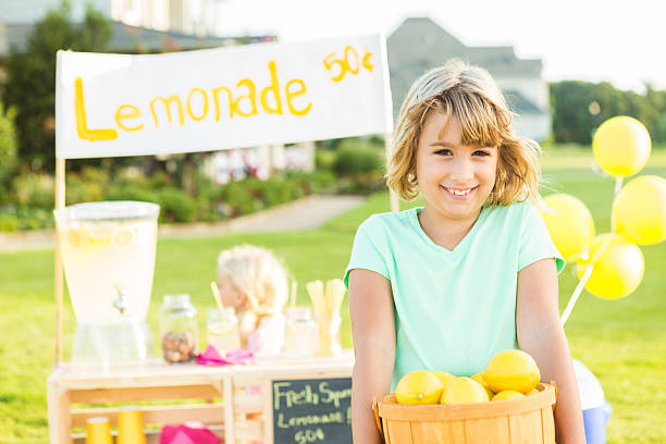 "Happy girl holding basket of lemons at her lemonade stand Pretty little girl with blonde hair wearing a mint colored shirt is holding up a basket full of bright yellow lemons. She is smiling directly at the camera. There is a lemonade stand behind her with a sign that says ""Lemonade 50 cents"" Her little sister is sitting at the lemonade stand with the money jar and all of the lemonade.They even have yellow balloons. lemonade stand stock pictures, royalty-free photos & images"