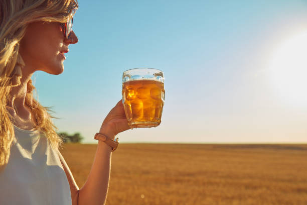 Happy girl holding beer glass in a big wheat-field. stock photo