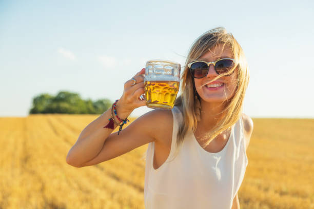 Happy girl holding beer glass in a big wheat-field. Happy girl holding beer glass in a big wheat-field. alternative pose stock pictures, royalty-free photos & images
