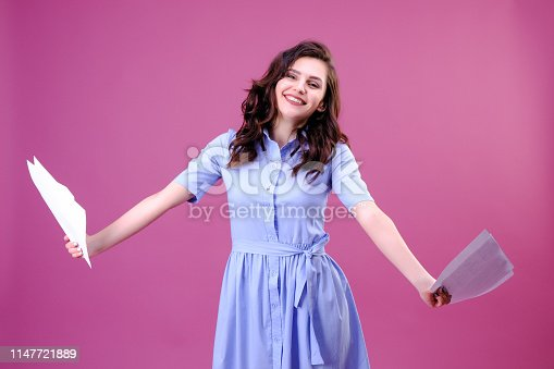 istock happy girl holding blank sheets of paper in two hands 1147721889