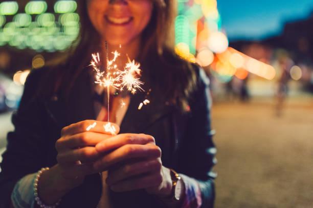 Happy girl holding burning sparklers stock photo