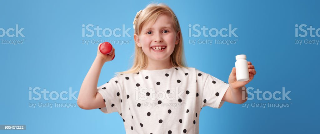 happy girl holding dumbbell and showing pills bottle on blue royalty-free stock photo