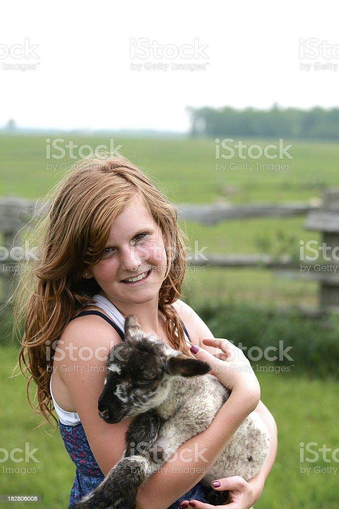 Happy Girl Holding Lamb in Field stock photo