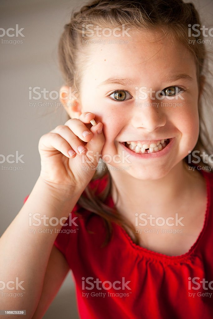 Happy Girl Holding Lost Tooth and Smiling stock photo