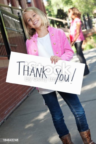 istock Happy girl holding thank you sign outside school building 184643248