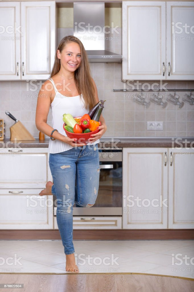 Happy girl holds in hands bowl with vegetable stock photo