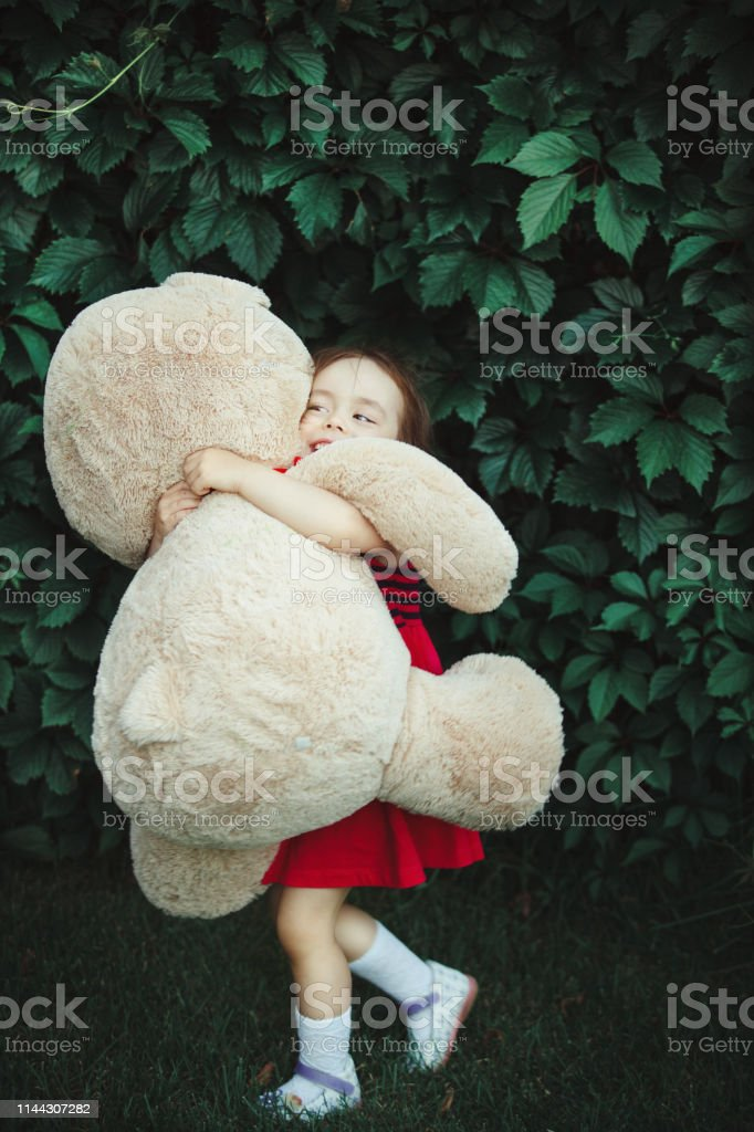 Happy girl hugging a big toy bear. cheerful child in nature.