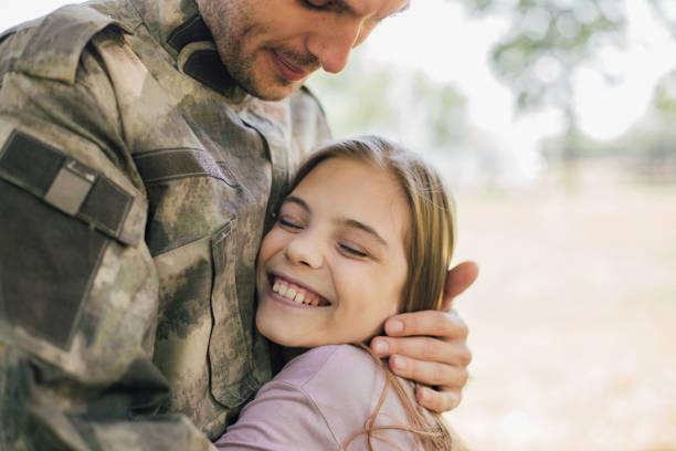 happy girl hugging a soldier - veterans day стоковые фото и изображения