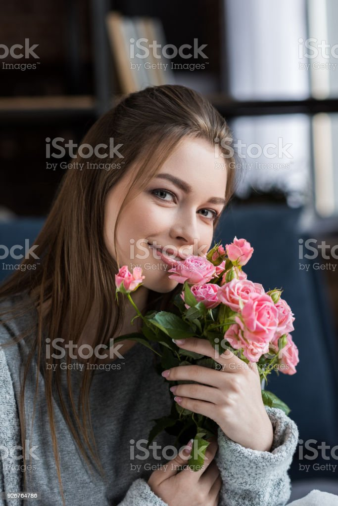 happy girl hugging bouquet of pink roses and looking at camera, 8 march concept стоковое фото