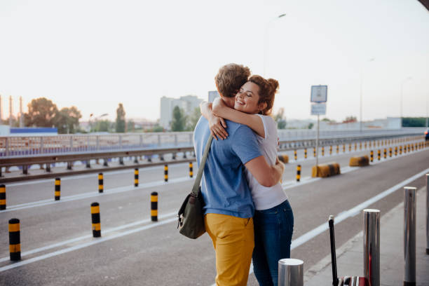 Happy girl hugging boyfriend after arrival from trip stock photo stock photo