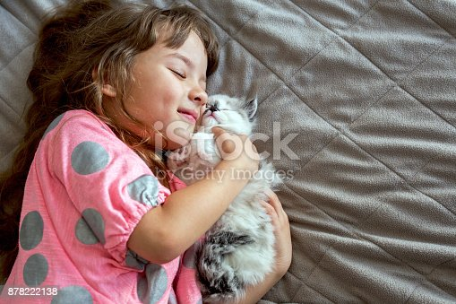 Smiling girl and little cat lying down on the bed.