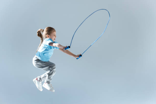 happy girl humping exercising with skipping rope on grey stock photo