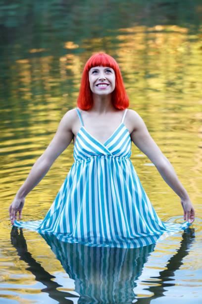 glückliches mädchen in einem see mit einem blauen drees - drees und sommer stock-fotos und bilder