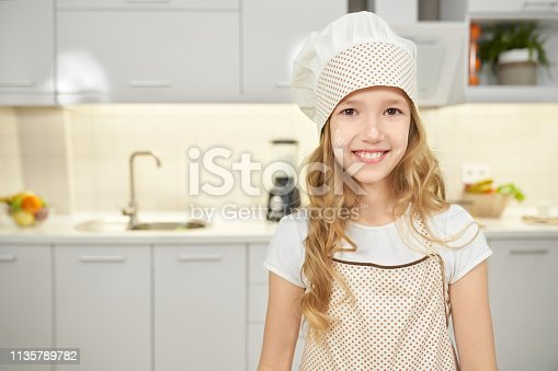 488109116istockphoto Happy girl in apron and chef hat posing in kitchen. 1135789782