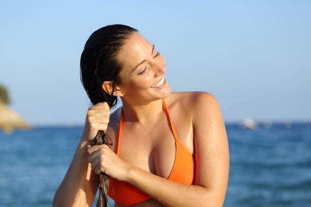 Happy girl in bikini draining hair after bath on the beach stock photo