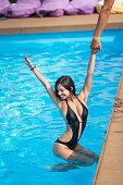 Happy girl in black bikini in the swimming pool holding a man's hand and having fun at sunny day, blurred background