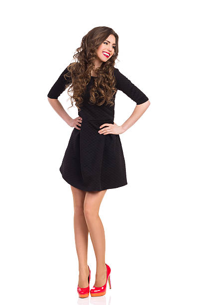 happy girl in black mini dress and red high heels - mini dress stock photos and pictures