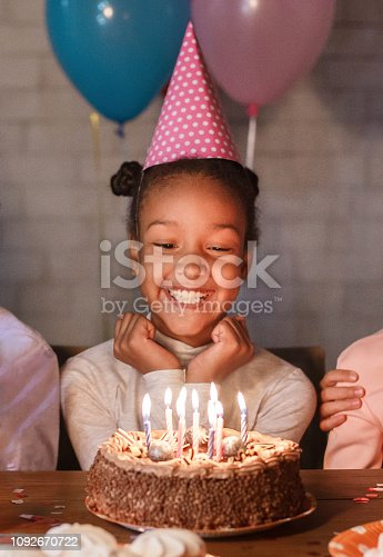istock Happy girl in party hat with birthday cake 1092670722