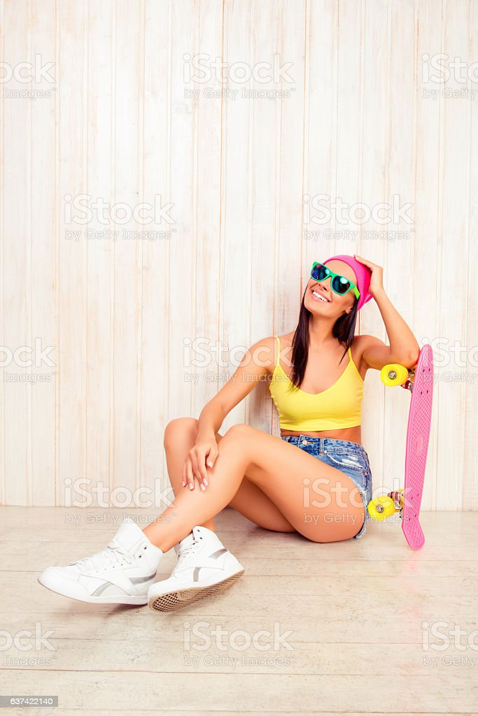Happy girl in pink cap  sitting on floor with  longboard стоковое фото
