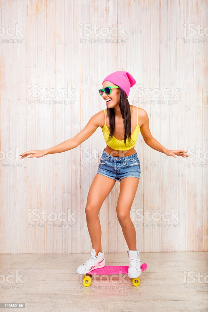 Cтоковое фото Happy girl in pink hat and glasses riding on skateboard