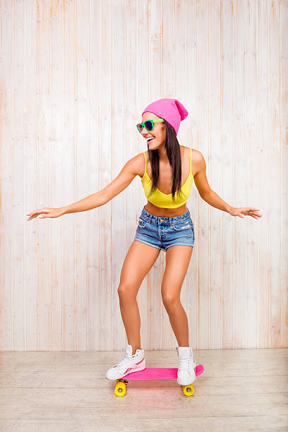 Happy girl in pink hat and glasses riding on skateboard – zdjęcie