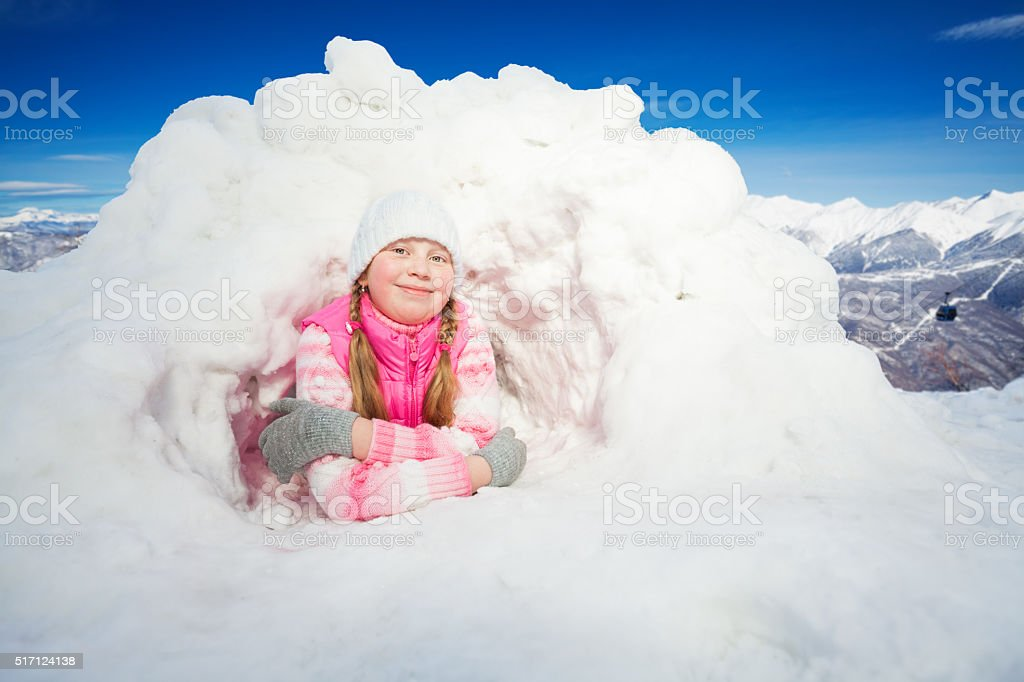 Happy girl in pink wear laying at the snow igloo stock photo
