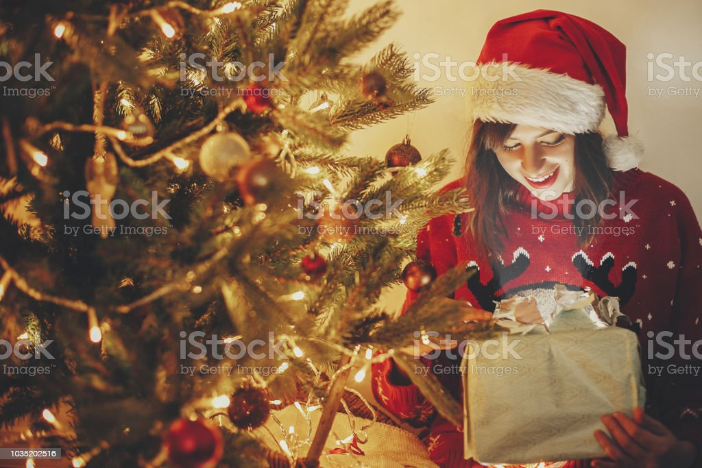 725914c375e99 Happy girl in santa hat opening magic Christmas gift box at golden  beautiful christmas tree with lights and presents in festive room. winter  atmospheric ...