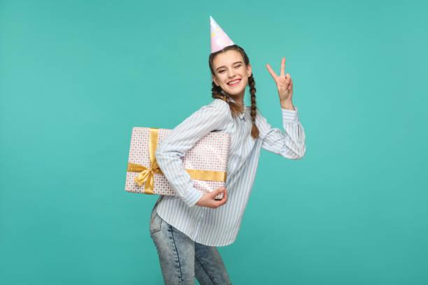 glückliches mädchen in gestreiften hemd mit gepunkteten geschenk-box und geburtstag kappe auf kopf stehen, blick in die kamera mit frieden oder siegeszeichen und toothy lächeln - jugendliche geburtstag geschenke stock-fotos und bilder