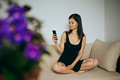 istock Happy girl in yellow using phone at home 1205026510