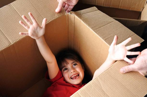 glückliches mädchen in einen großen karton, umzug in ein neues haus - kinder verpackung stock-fotos und bilder