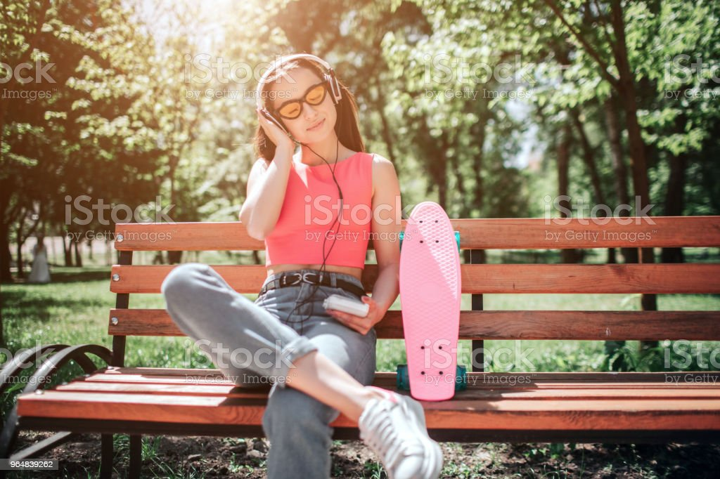 Happy girl is enjoying the moment. She is listening to music through headphones and enjoying the moment. She has put right leg on left one. There is a pank skate standing on bench royalty-free stock photo