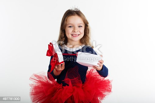 1061876006istockphoto Happy girl is holding gift box with red ribbon 497781300